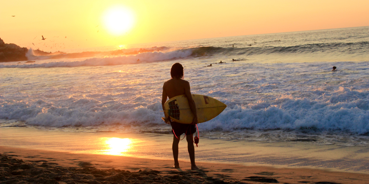 Surfer at sunset in Puerto Escondido